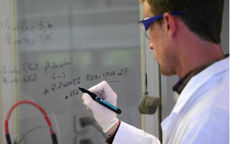 Naukowiec notuje skład leku na tablicy - Działalność naukowa Biocodex