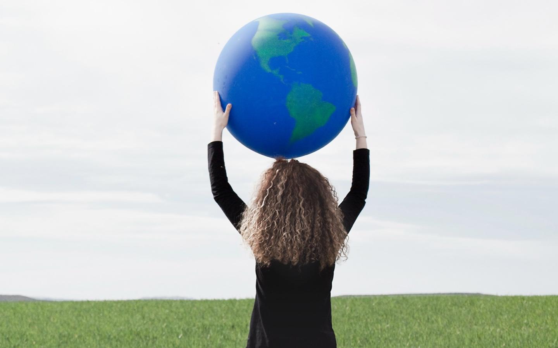 Kobieta trzyma na głowie globus - sekcja Rozwój międzynarodowy Biocodex
